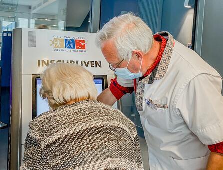 afbeelding vrijwilliger helpen aan kiosk